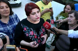 FILE - Azerbaijani investigative reporter Khadija Ismayilova, center, speaks to journalists in Baku, Azerbaijan, May 25, 2016.