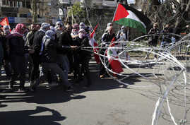 Protesters try to remove barbed wire that blocks a road leading to the U.S. Embassy during a protest against President Donald Trump's Middle East peace plan, in Aukar, east of Beirut, Lebanon, Feb. 2, 2020.