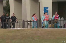 FILE - This photo taken from video provided by WEAR-TV shows emergency responders following a shooting incident at Naval Air Station Pensacola, in Pensacola, Florida, Dec. 6, 2019.