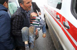 A man carries a wounded boy to an ambulance after an earthquake hit villages in Baskale town in Van province, Turkey, at the border with Iran, Feb. 23, 2020.