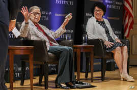Supreme Court Justice Ruth Bader Ginsburg, left, holds up her hands as she and Supreme Court Justice Sonia Sotomayor arrive to…