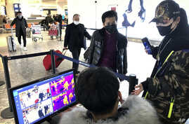 FILE - A man passes through a health screening checkpoint at Wuhan Tianhe International Airport in Wuhan, in southern China's Hubei province, Jan. 21, 2020.
