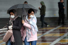 Women wear masks to protect themselves against the coronavirus, as they cross a street in Tehran, Iran, Feb. 25, 2020.