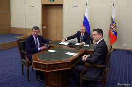 FILE - Russian President Vladimir Putin, center, then-Deputy Prime Minister of Russia Dmitry Kozak, left, are seen participating in a video conference in Sochi, Russia, Dec. 2, 2019. At right is Russian Energy Minister Alexander Novak.