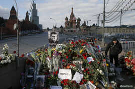 FILE - A man walks past flowers at the site where Kremlin critic Boris Nemtsov was murdered on Feb 27, 2015, at the Bolshoi Moskvoretsky Bridge, with St. Basil's Cathedral seen in the background, in central Moscow, Russia, March 6, 2015.