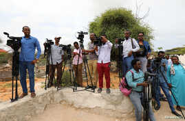 FILE - Somali journalists are seen during a stake-out on the outskirts of Mogadishu, Somalia, July 25, 2019.