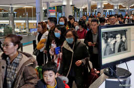 Passengers from China pass by a thermal screening point upon their arrival at Istanbul International Airport in Istanbul, Turkey, Jan. 24, 2020.