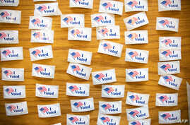 """""""I Voted"""" stickers cover a table at a polling station during the North Carolina primary on Super Tuesday in Charlotte, North…"""