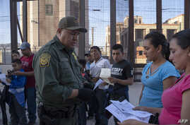 (FILES) In this file photo taken on May 16, 2019  US Customs and Border Protection agent checks documents of a small group of…