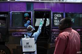 A government health official sprays a chlorine solution on a public transport vehicle as a preventive measure against the COVID…