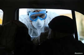 A member of the medical team checks the temperature of an old man in a car, following the coronavirus outbreak, at a checkpoint