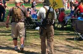 Two men carrying semiautomatic rifles attend a gun rights rally Saturday, April 14, 2018, outside the state capitol in Dover, Del.