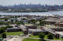FILE - This June 20, 2014 file photo shows the Rikers Island jail complex in New York with the Manhattan skyline in the background.