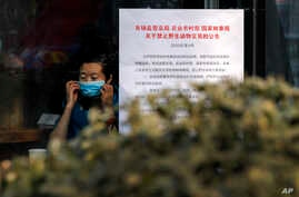 "A woman puts on a mask near a notice board that reads ""Bans on wild animals trading following the coronavirus outbreak"" at a cafe in Beijing, Monday, Feb. 10, 2020."