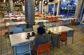 A customer eats a bowl of soup at a deserted food court in the Koreatown section of Los Angeles, Feb. 27, 2020.