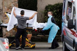 A staff member blocks the view as a person is taken by a stretcher to a waiting ambulance from a nursing facility