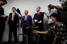 The Tokyo 2020 Organizing Committee's Toshiro Muto, center left, and Yoshiro Mori, center right, listen to questions from the media during a news conference in Tokyo, March 4, 2020.