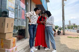 Women from the the Hui Muslim ethnic minority from a nearby neighborhood gather outside a shop near an OFILM factory in Nanchang in eastern China's Jiangxi province, June 5, 2019.