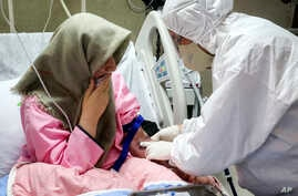 FILE - a medic wearing protective gear treats a patient infected with the new coronavirus, attends a patient