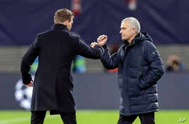 Tottenham's manager Jose Mourinho, right, Leipzig's head coach Julian Nagelsmann touch their forearms instead of shaking hands