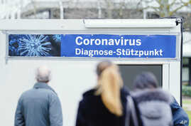 "People stand in front of containers with a banner reeding ""Coronavirus Diagnosis Base"" on the grounds of the University…"