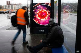 Two men wait at a bus stop with a screen displaying a symbol photo of the novel coronavirus in Berlin, Germany, March 12, 2020.