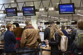 People wait to check in to a flight to Chicago at the United Airlines counter in the main terminal of Brussels International…
