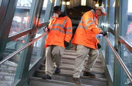 Employees of Metro-North Railroad disinfect handrails at the New Rochelle Metro-North station in New Rochelle, N.Y., Thursday,…