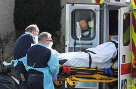 A person is loaded into an ambulance, March 12, 2020, at the Life Care Center in Kirkland, Wash., near Seattle.