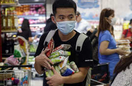 A man wearing a protective mask looks for the start of the queue at a grocery store in Taguig, metropolitan Manila, Philippines, March 13, 2020.