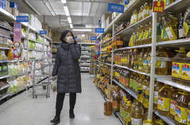 A shopper wearing a face mask browses an aisle of cooking oil in a supermarket in Beijing on March 16, 2020.