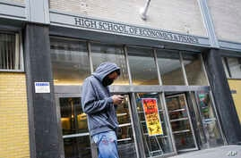 A pedestrian wears a face mask while standing outside the High School of Economics & Finance closed due to coronavirus concerns, Monday, March 16, 2020, in New York.