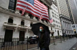 A man wearing a mask walks by the New York Stock Exchange, March 17, 2020.