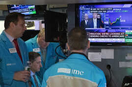 Traders at the New York Stock Exchange listen to President Donald Trump's televised White House news conference, Tuesday, March…