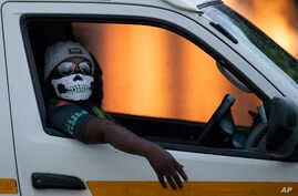 A minibus taxi driver wearing a face musk looks on during his journey in Kwa-Thema east of Johannesburg, South Africa, Tuesday,…