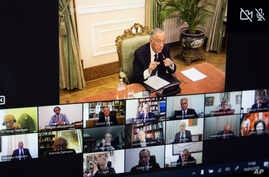 Portuguese President Marcelo Rebelo de Sousa, top, appears on a screen while holding a videoconference with the special advisory body Council State in the Belem palace in Lisbon, Portugal, March 18, 2020.