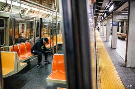 "A subway customer wears protective gloves on an empty car as it stops at a sparsely populated 57th Street station due to COVID-19 concerns, Friday, March 20, 2020, in New York. Gov. Andrew Cuomo is ordering all workers in non-essential businesses to stay home and banning gatherings statewide. ""Only essential businesses can have workers commuting to the job or on the job,"" Cuomo said of an executive order on Friday. Nonessential gatherings of individuals of any size or for any reason are canceled or postpone"
