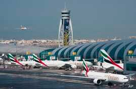 FILE - An Emirates jetliner comes in for landing at Dubai International Airport in Dubai, United Arab Emirates.