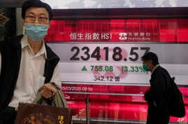 A man wearing a face mask walks past a bank's electronic board showing the Hong Kong share index at Hong Kong Stock Exchange Wednesday, March 25, 2020.
