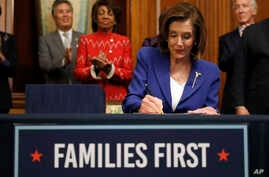 House Speaker Nancy Pelosi of Calif. accompanied by legislators, signs the Coronavirus Aid, Relief, and Economic Security bill.