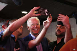 U.S. Democratic presidential candidate and former Vice President Joe Biden takes selfies with customers at Roscoe's Chicken and…
