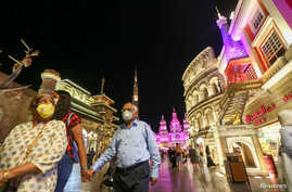 People wear protective masks, following an outbreak of coronavirus, as they walk at Global Village in Dubai, United Arab Emirates, March 10, 2020.