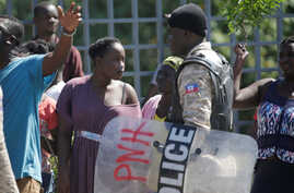 A resident looks at a Haitian National Police (PNH) officer during a small protest outside of Monte Cristo Hotel, designated as…