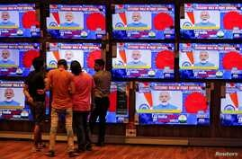 People watch Indian Prime Minister Narendra Modi addressing the nation amid concerns about the spread of coronavirus disease …
