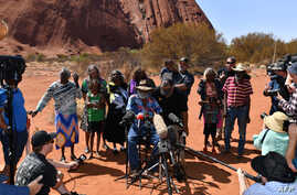 FILE - Australian Aboriginals speak to members of the media at Uluru-Kata Tjuta National Park in Australia's Northern Territory, Oct. 26, 2019.