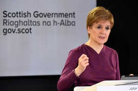 FILE - Scotland's First Minister Nicola Sturgeon gestures as she holds a briefing on the coronavirus outbreak in Edinburgh, March 26, 2020.