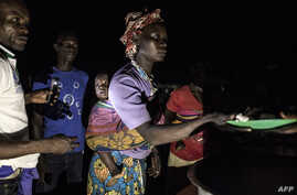FILE - South Sudanese refugees receive food after being transported from the border of South Sudan and the Democratic Republic of the Congo (DRC) to a refugee settlement site in Aru, DRC, May 10, 2019.
