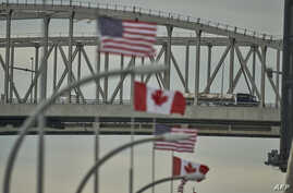 A truck crosses the U.S.-Canada Bluewater Bridge border crossing between Sarnia, Ontario, and Port Huron, Michigan, March 16, 2020. The border between the two countries is now closed to non-essential travel.