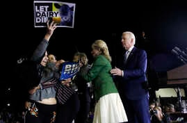 A protester is held back by Biden's adviser Symone Sanders, wearing stripes, and his wife Jill, 2nd right, as Democratic presidential candidate former Vice President Joe Biden stands (R) during a primary election night rally in Los Angeles, March 3, 2020.