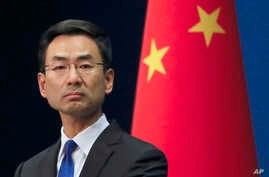 Chinese Foreign Ministry spokesman Geng Shuang listens to a question from a reporter during a daily briefing at the Ministry of Foreign Affairs office in Beijing, March 18, 2020.